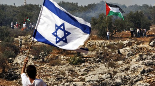 Israeli flag bearer and a Palestinian Flag Bearer in the background